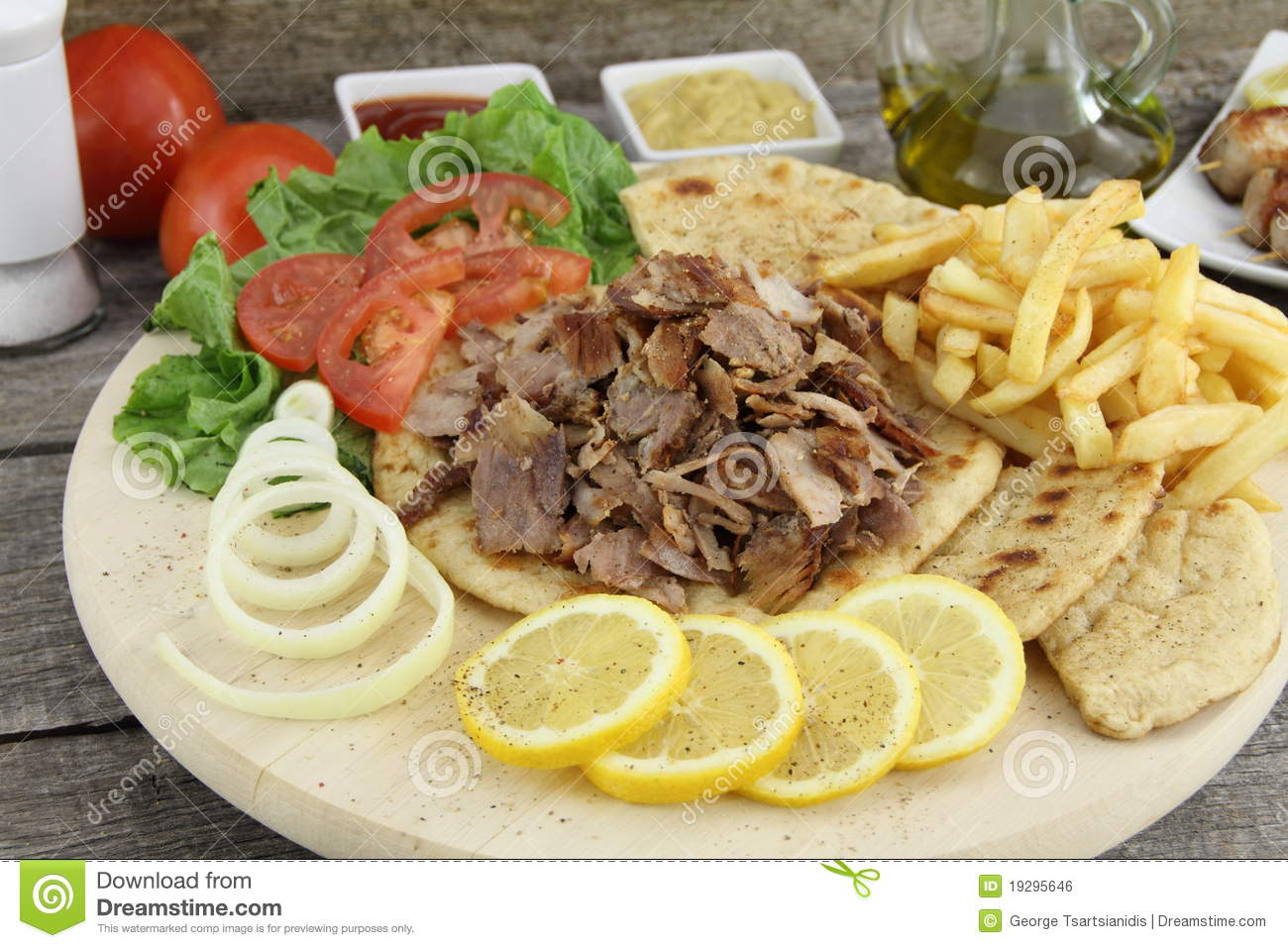 Plate of traditional Greek gyros with meat, fried potatoes, tomato and ...