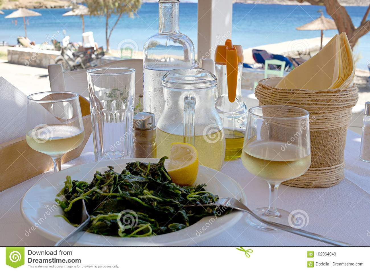 Greek khorta, white wine on restaurant table near the sea. Dodecanese Islands