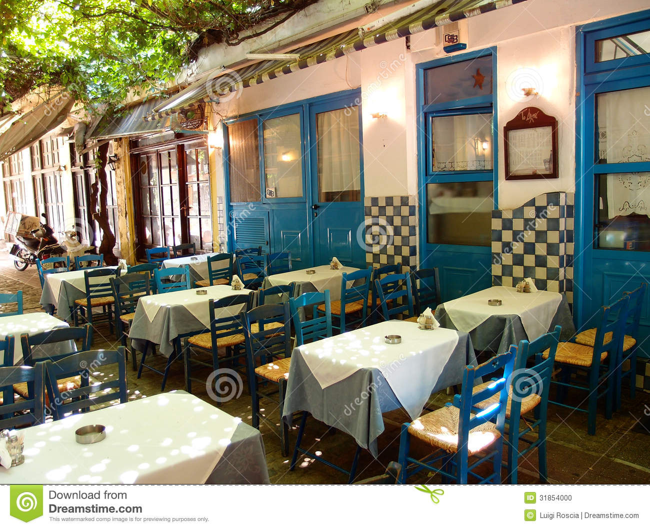 Typical Greek Restaurant With Simple Wooden Tables And Chairs Painted
