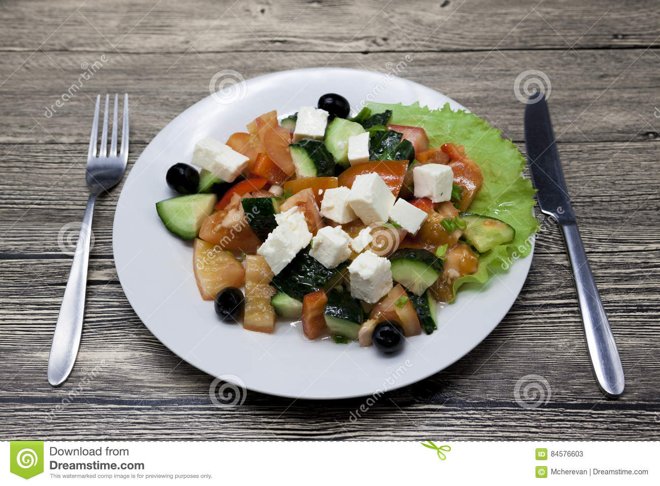Greek salad on a white plate with fork and knife on a for Apollon greek and european cuisine