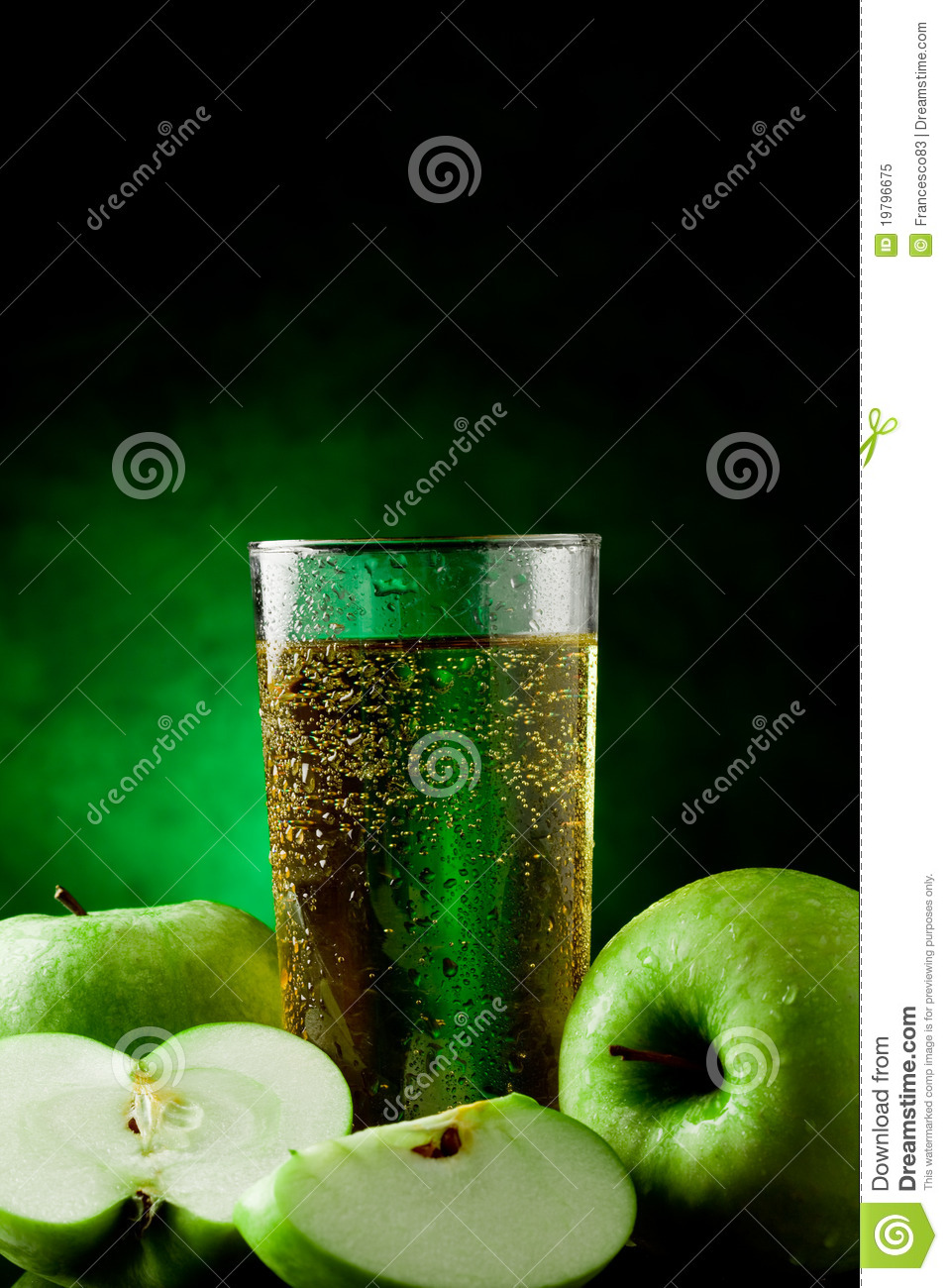 Fresh sparkling green apple juice on green spot lighted background.
