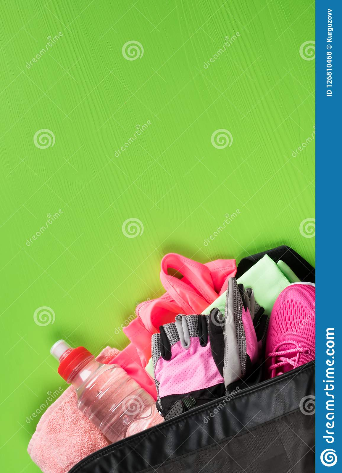 On a green background, a set of female sporting things of pink color in an open bag with a bottle of water