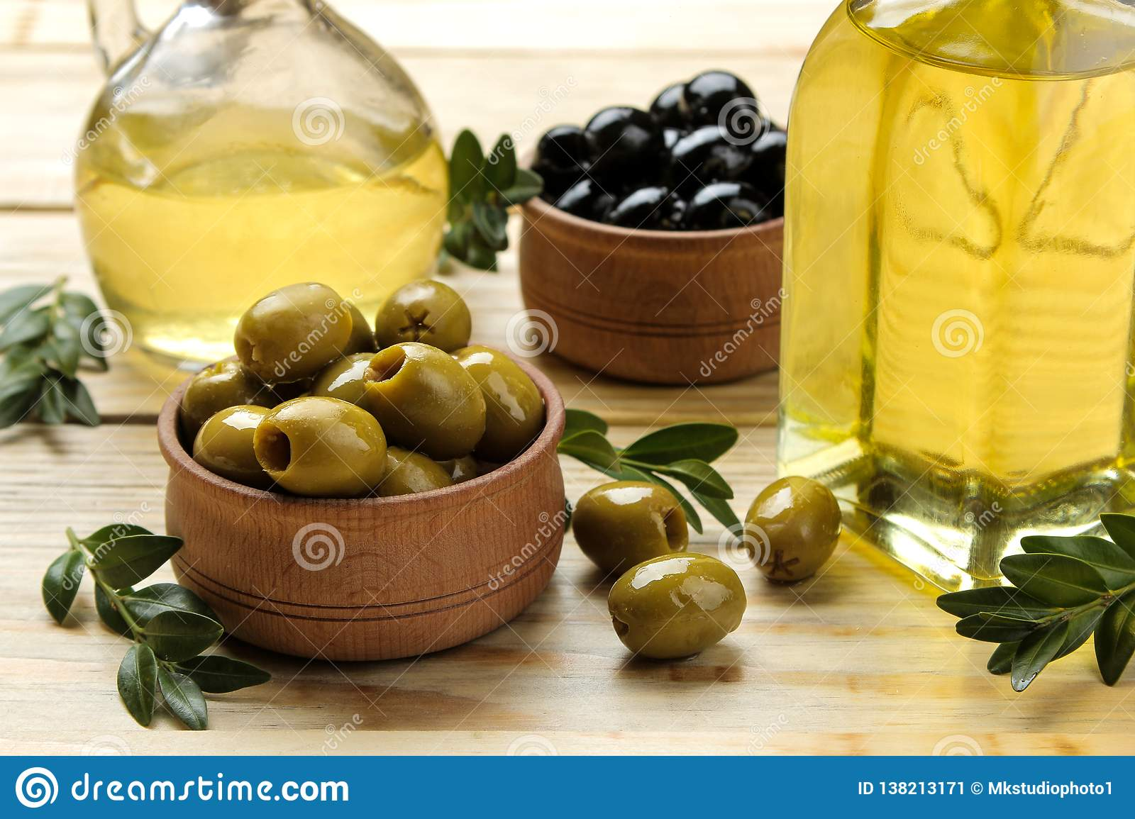 b1d9d15567d4 green and black olives in a wooden bowl with olive oil on a natural wooden  table