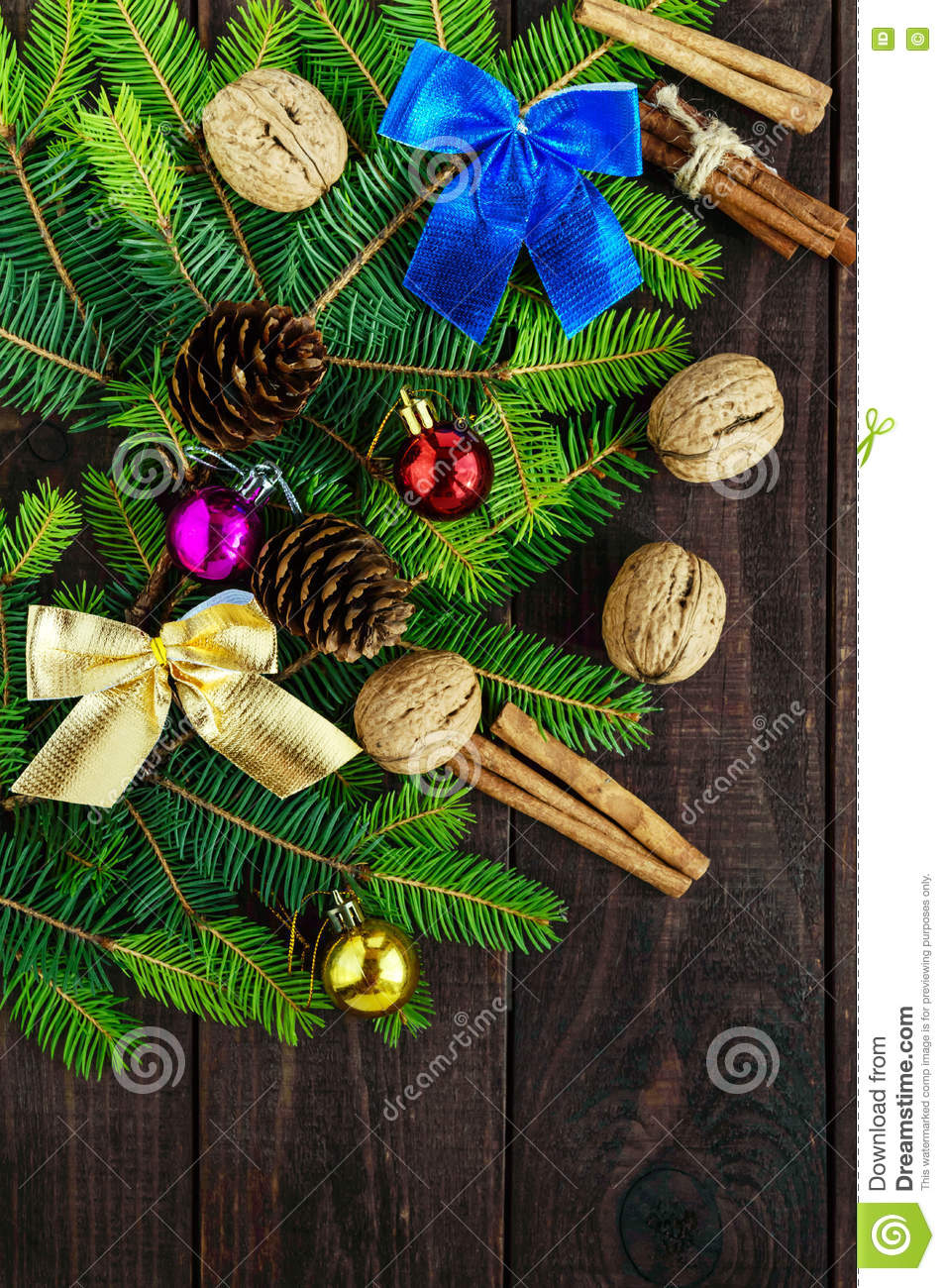 Green branch of fir, decorated with bright ribbons, balls, nuts, pine cones, cinnamon on dark wooden background.