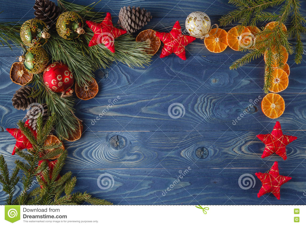 Green branch and red xmas decorations on boards