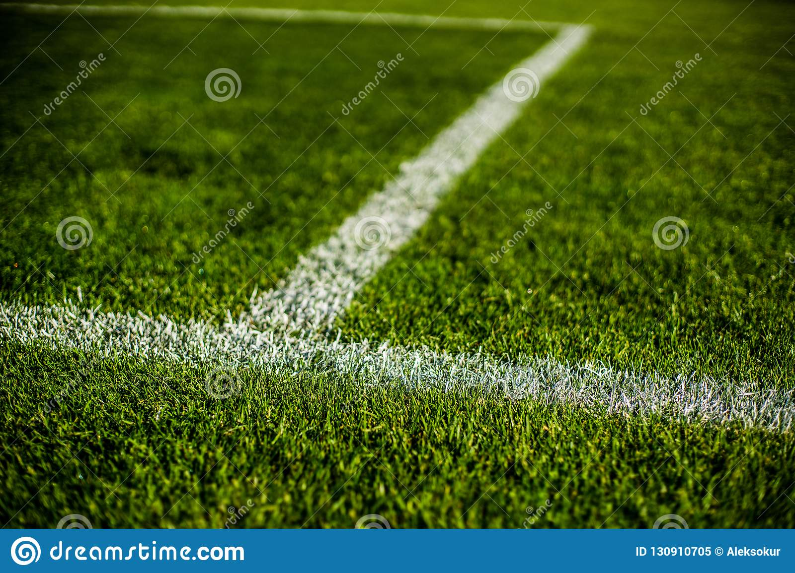Green bright colorful grass pitch of football stafium, close up with beautiful bokeh