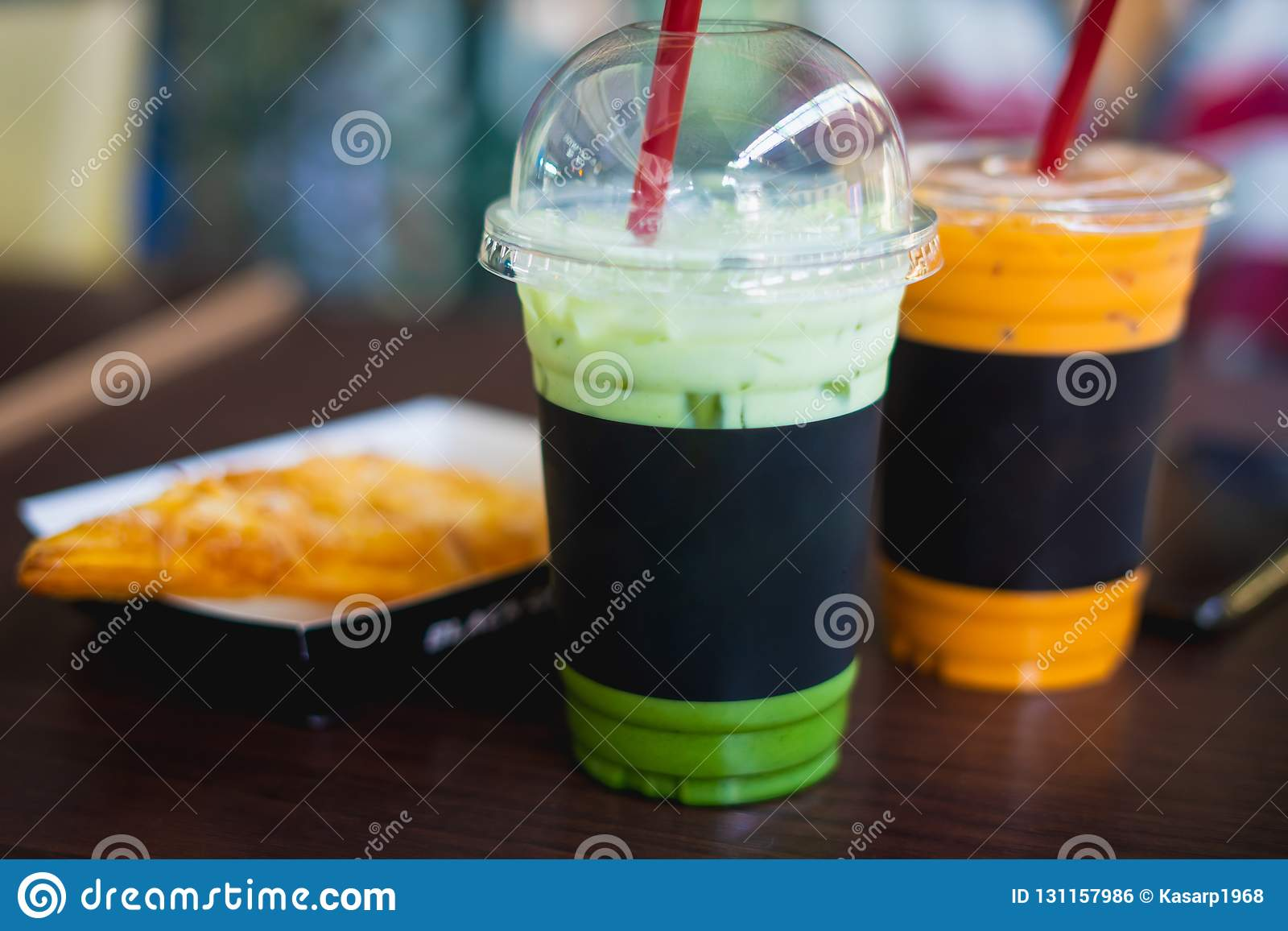 Green bubble tea in plastic cups on wooden table.The beautiful p