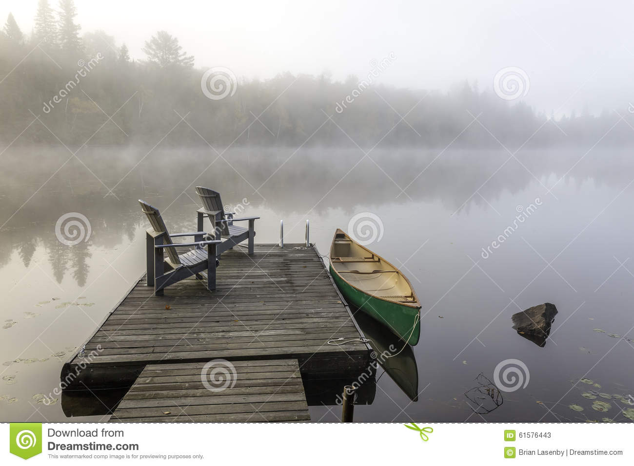 Green Canoe And Dock On A Misty Morning Stock Image