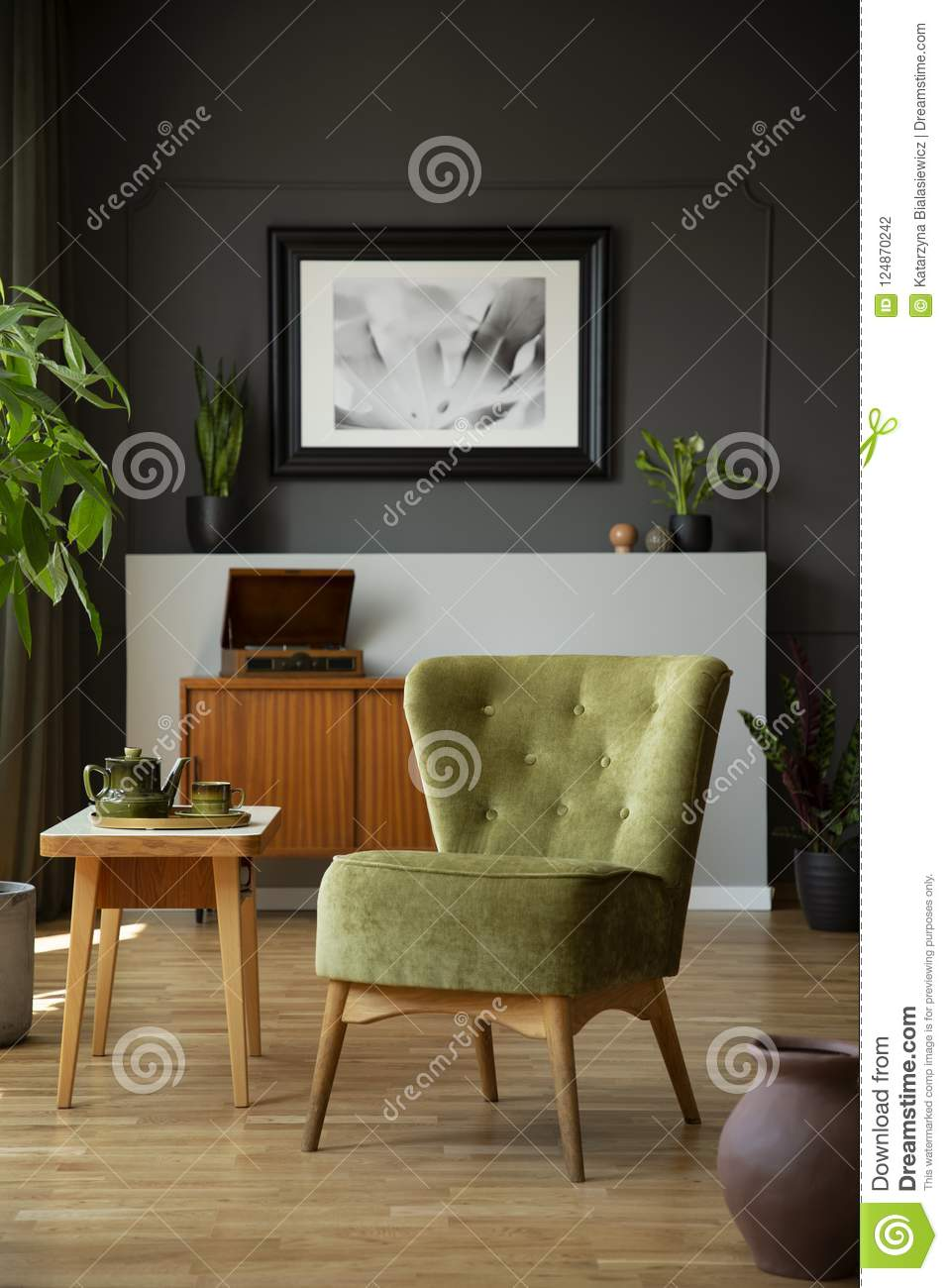 Green Chair Next To Wooden Table In Dark Living Room