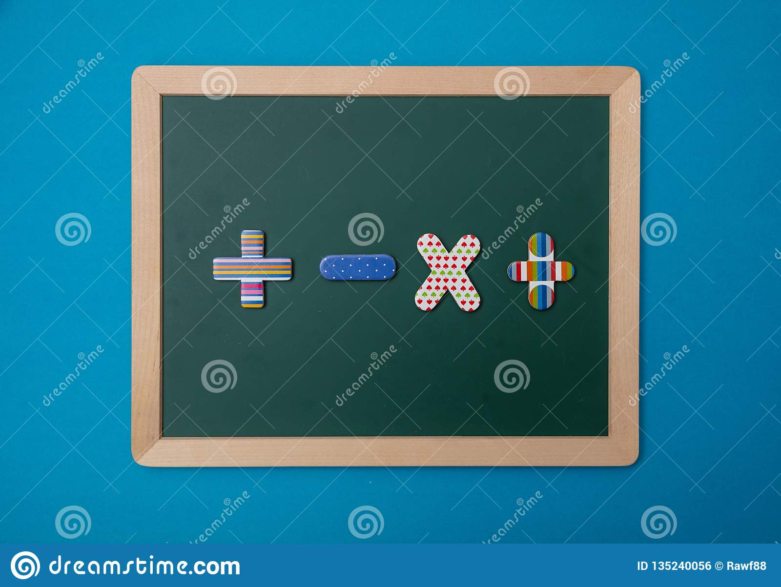 Green chalkboard with wooden frame, colorful math operation signs