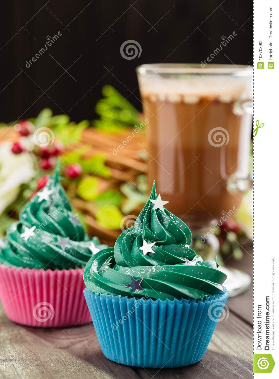 Green christmas cupcake with festive decorations and glass of co
