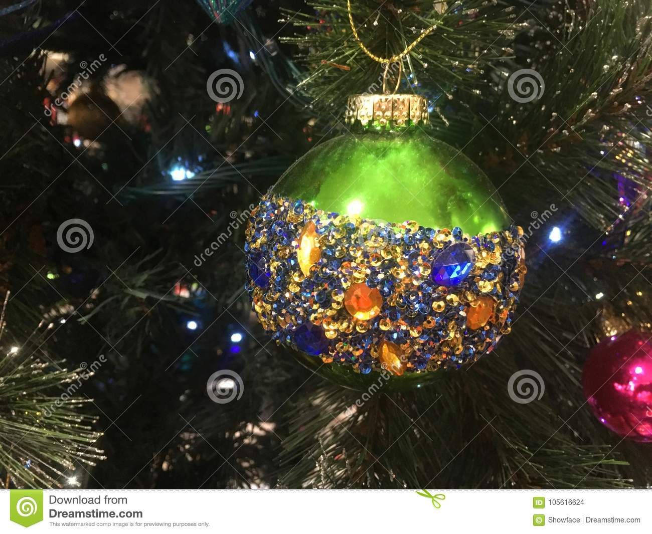 Green Christmas tree bauble embellished with amber blue and gold