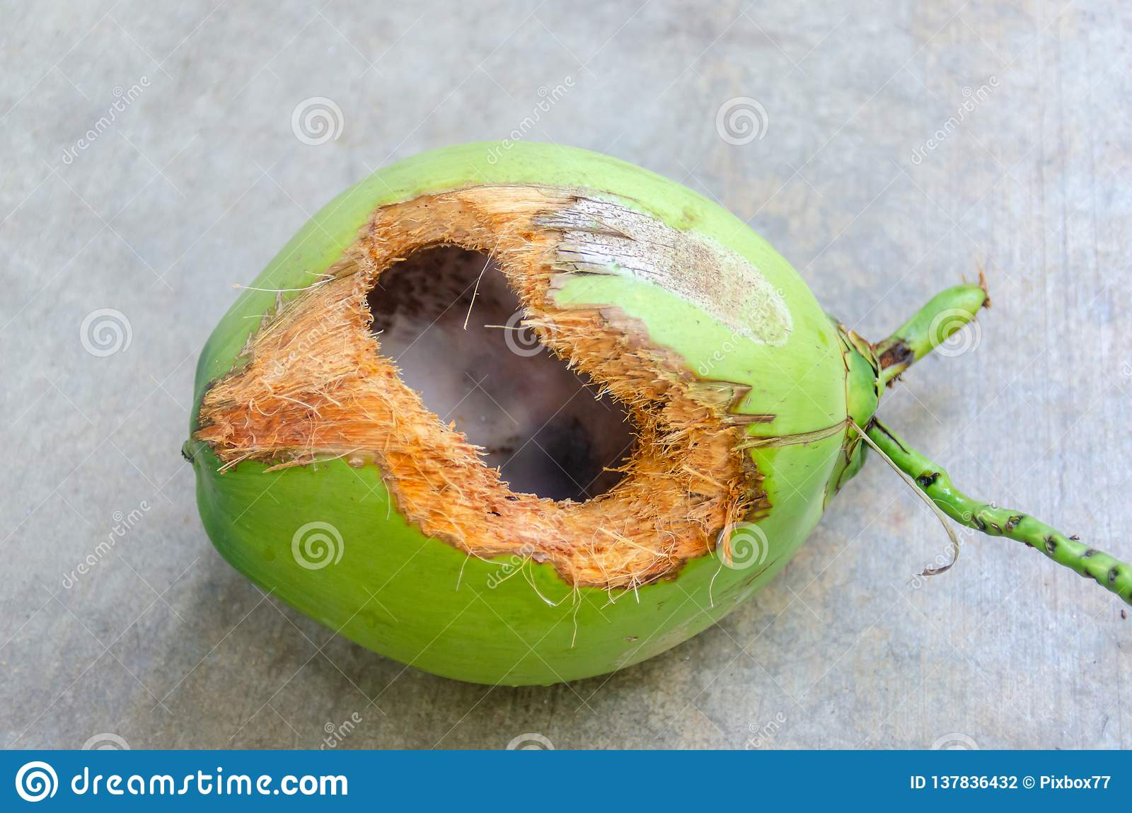 Green coconut with hole on ground