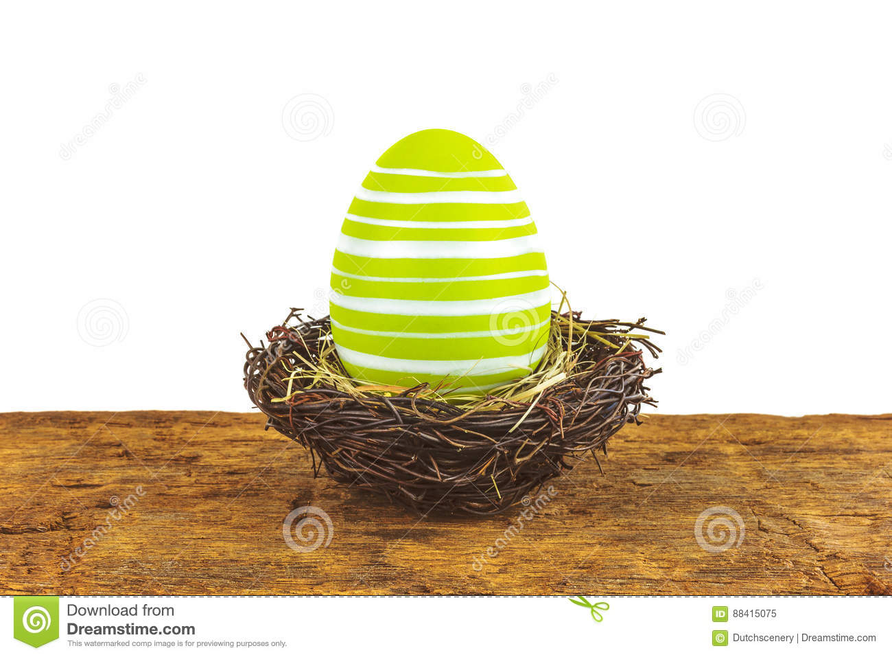 Green easter egg on a wooden table isolated on white
