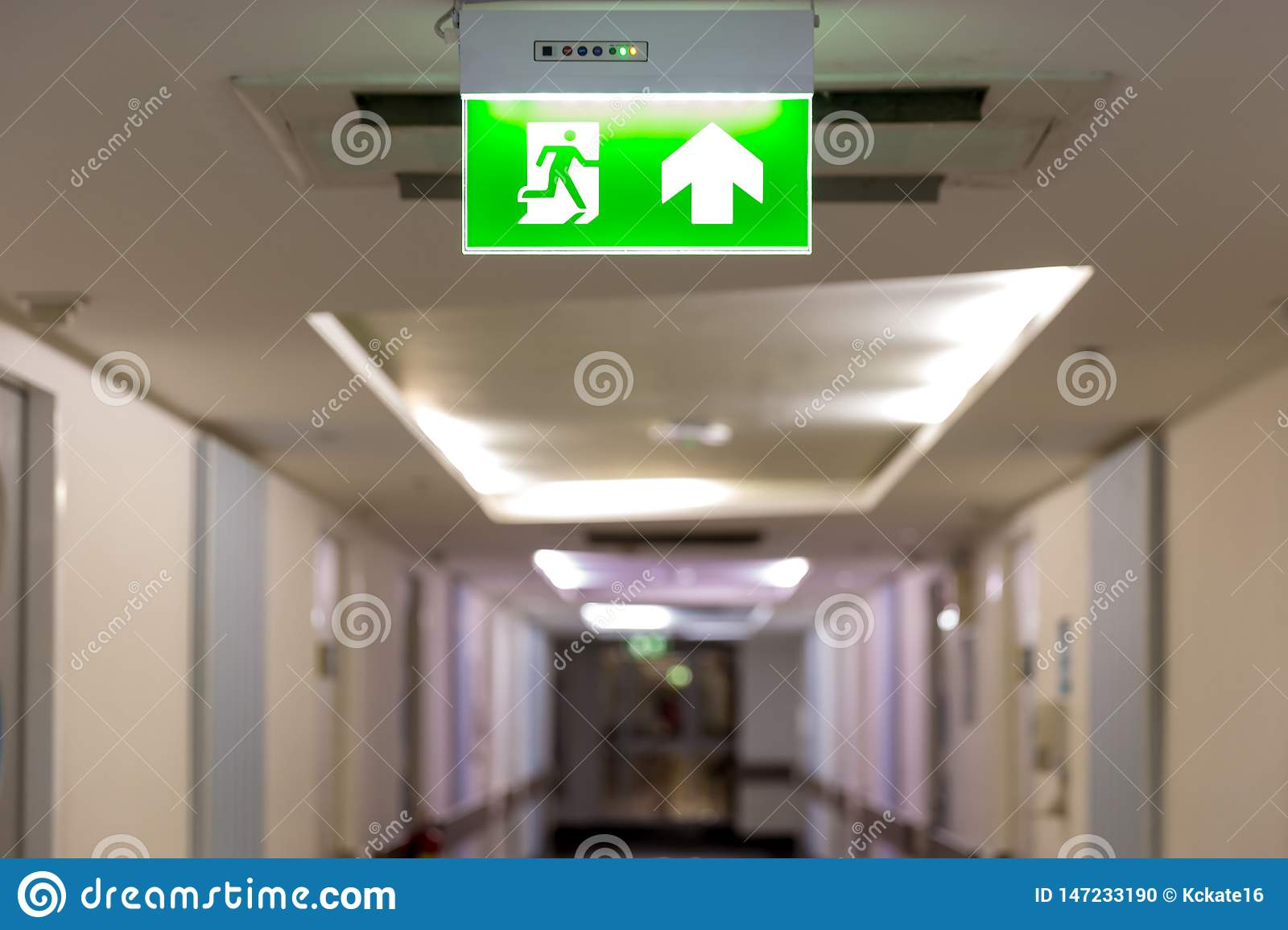 Green emergency exit sign showing the way to escape.Fire exit in the building