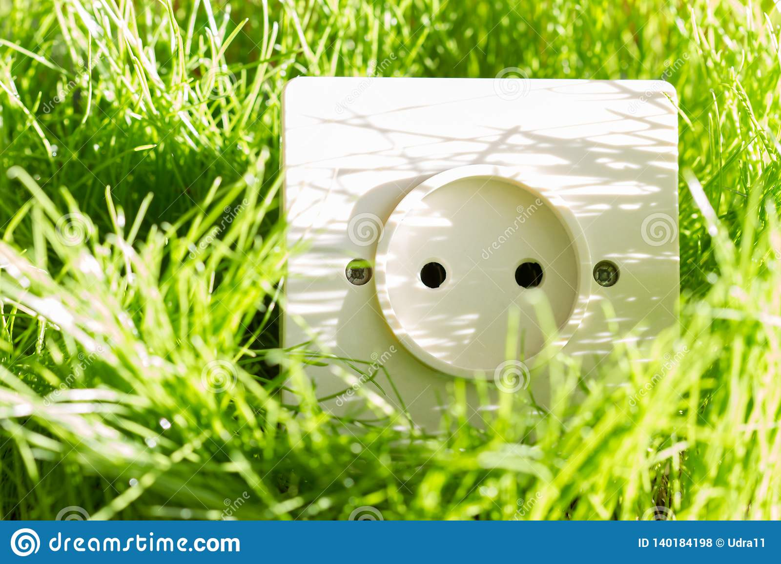 Green energy concept with socket in the grass outdoor