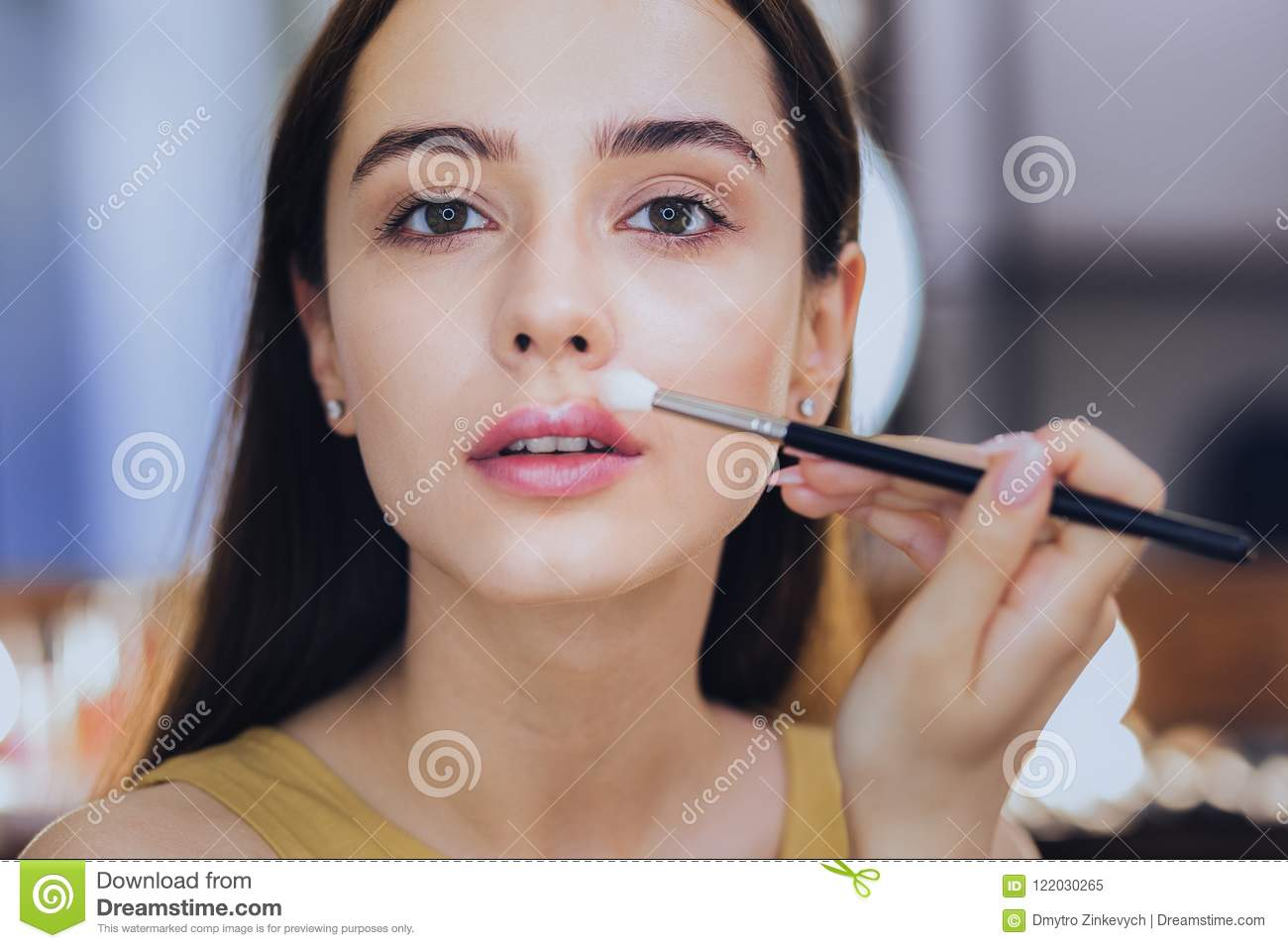 Green-eyed appealing woman holding little face brush in her hand