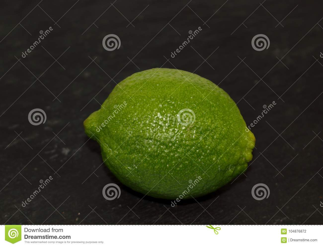 Green fresh exotic citrus fruit lime on a black background