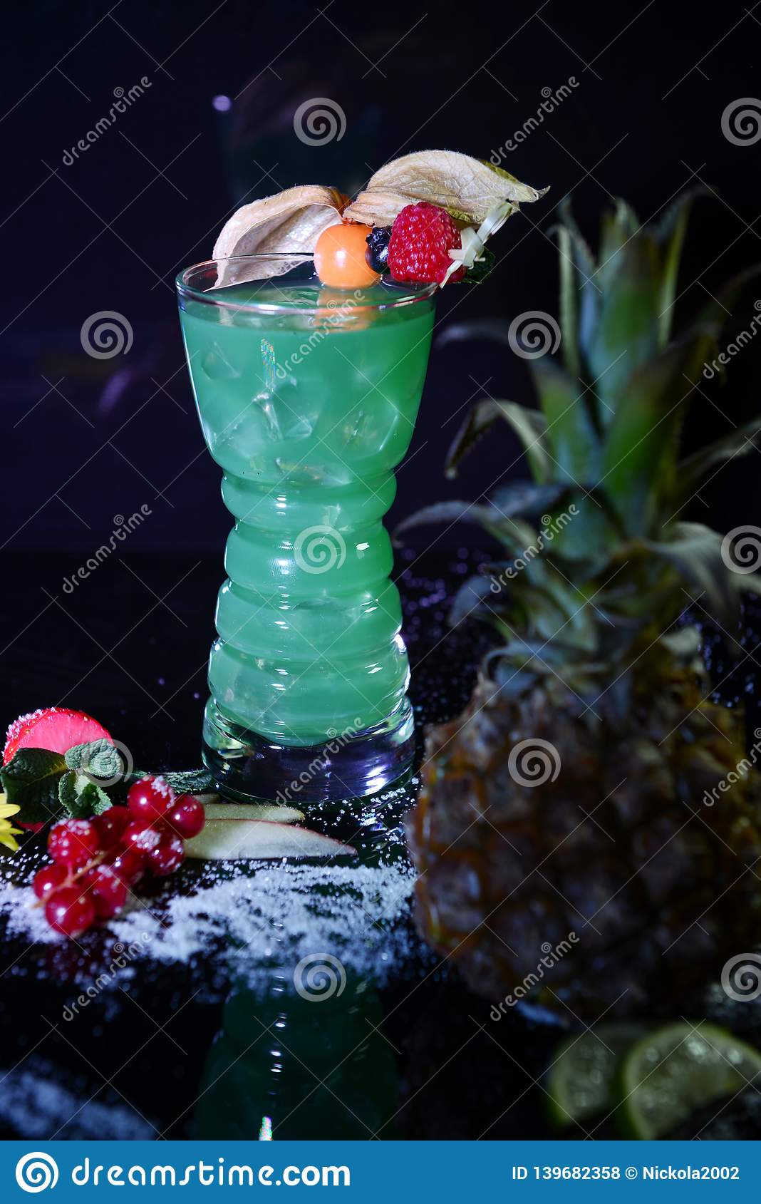 Neon green cocktail with fruits on black background