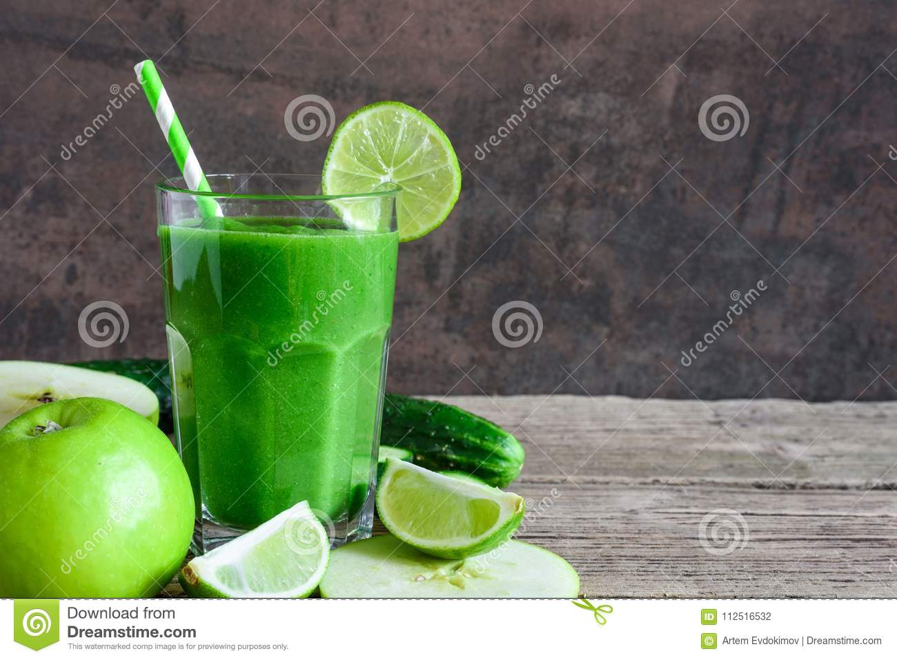 Green healthy smoothie in a glass with spinach, apple, cucumber and lime with a straw. detox drink