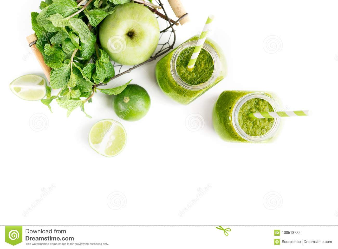 Green healty drink in two mason jars with green apple, mint and lime on white background. Vegetarian food concept. Detox