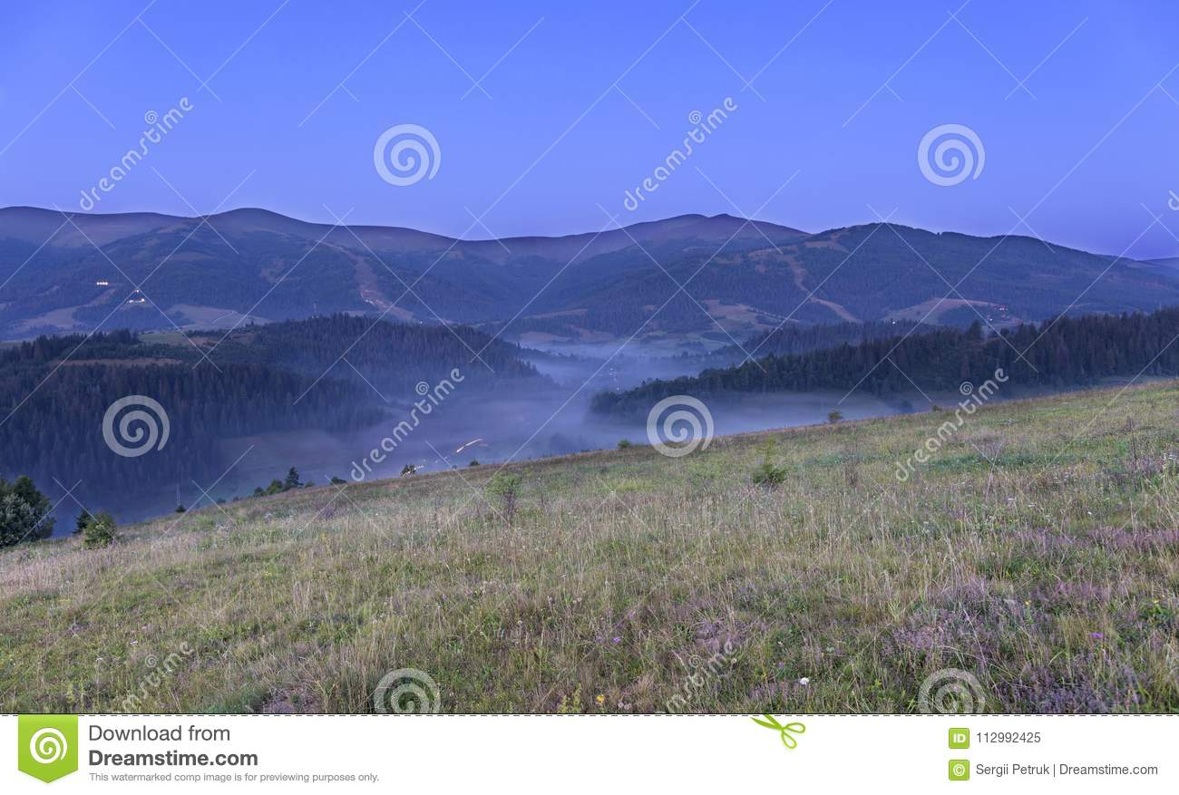 A green meadow and a gray curly fog on a hill in the background of the Carpathian Mountains in the early morning