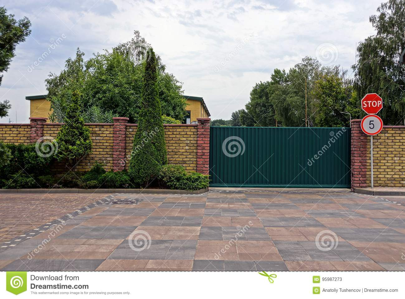 Green Iron Gates And Road Signs Near A Brick Wall With