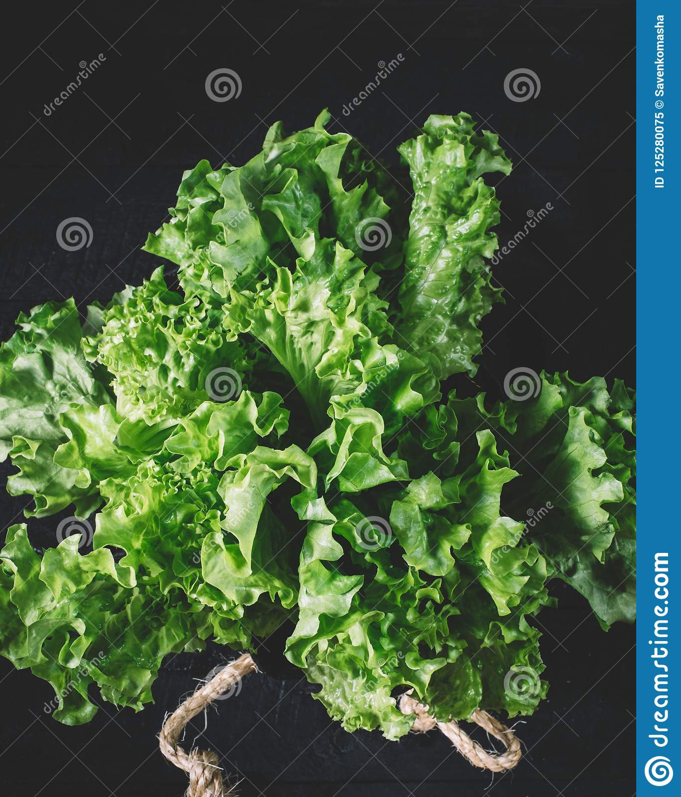Green lettuce leaves on a background of white brick wall, fresh healthy salad food on kitchen table, space mock up, dieting leaf