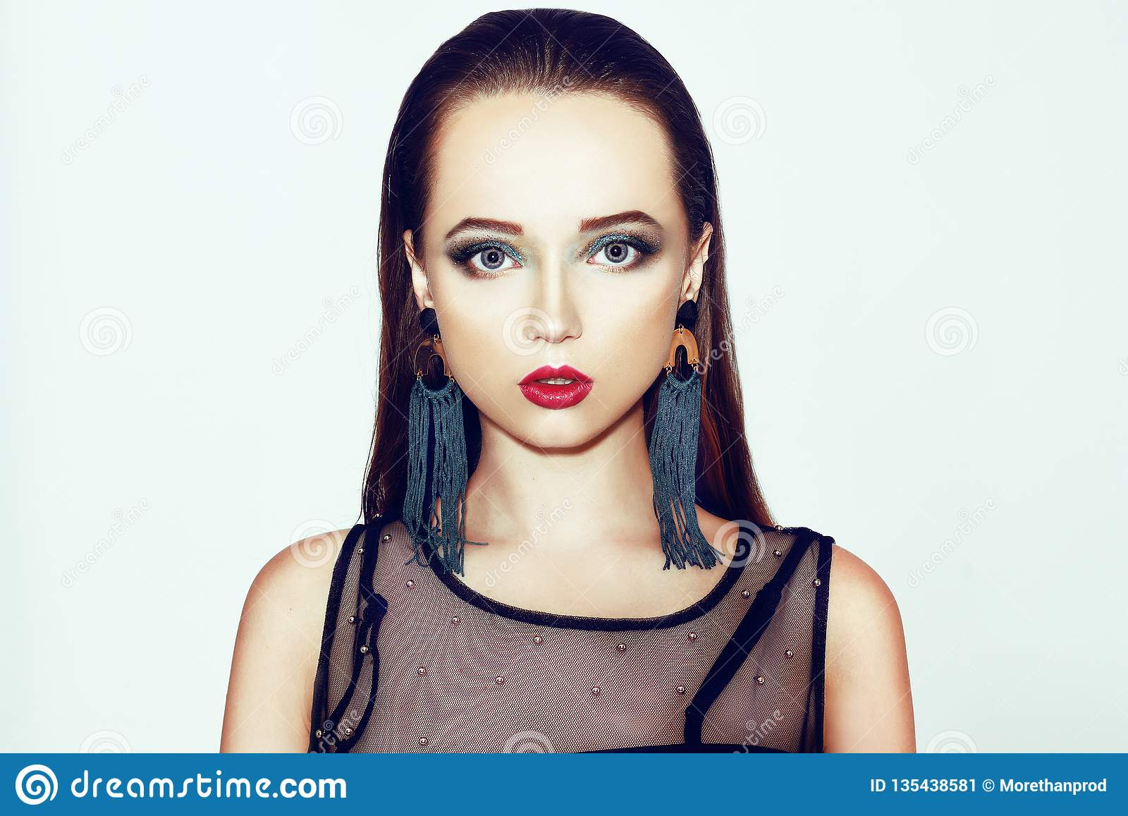 Green makeup. Beautiful girl with makeup isolated on background. Eye make-up and sensual lips. Elegant hairstyle. Brunette