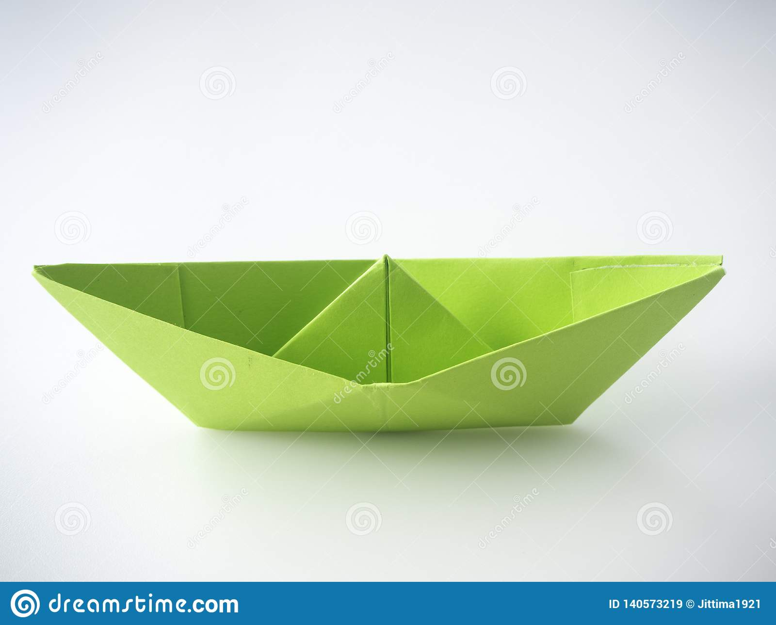Green paper boat laid on white