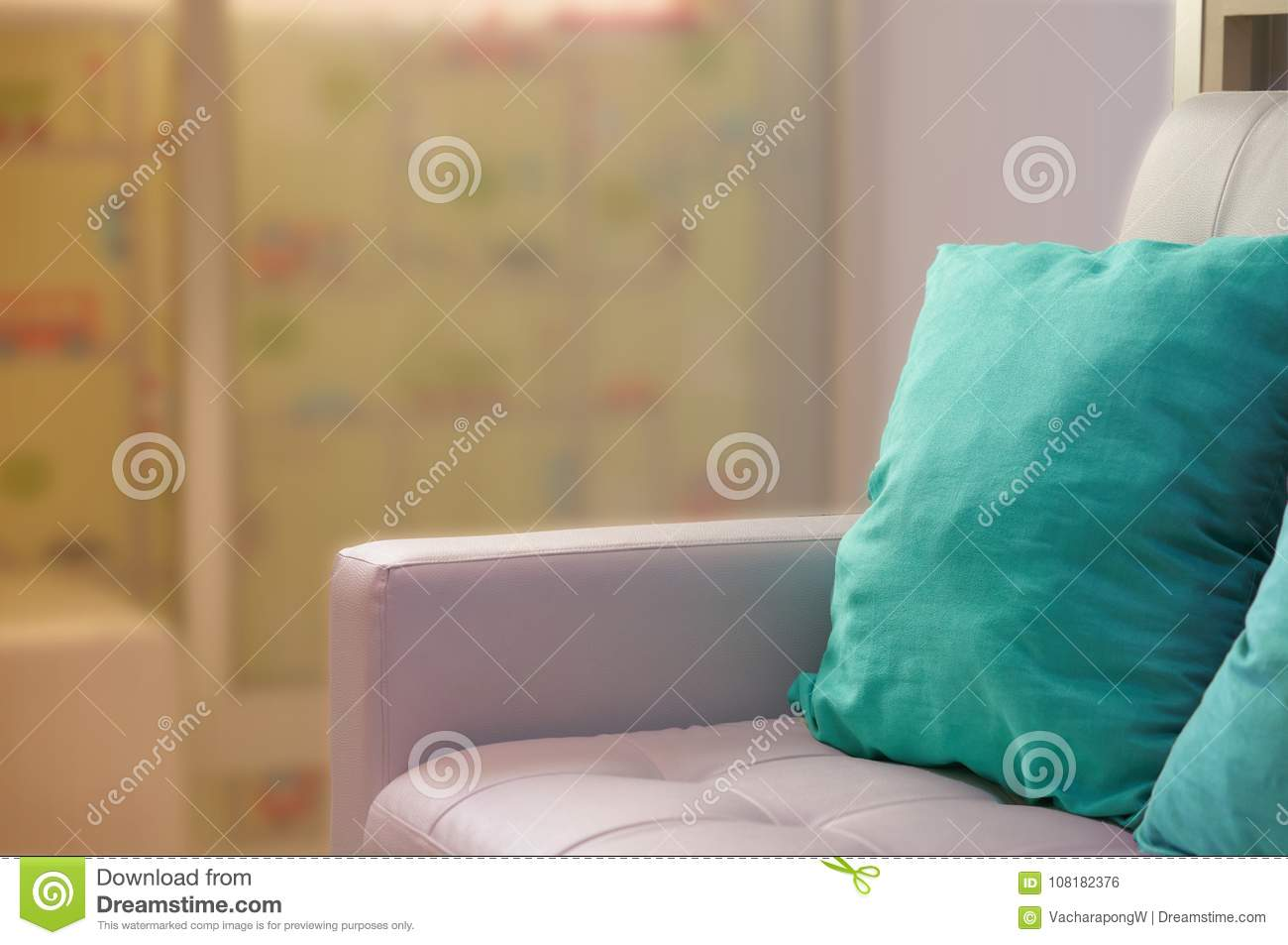 Green pillows on white sofa beside glass door