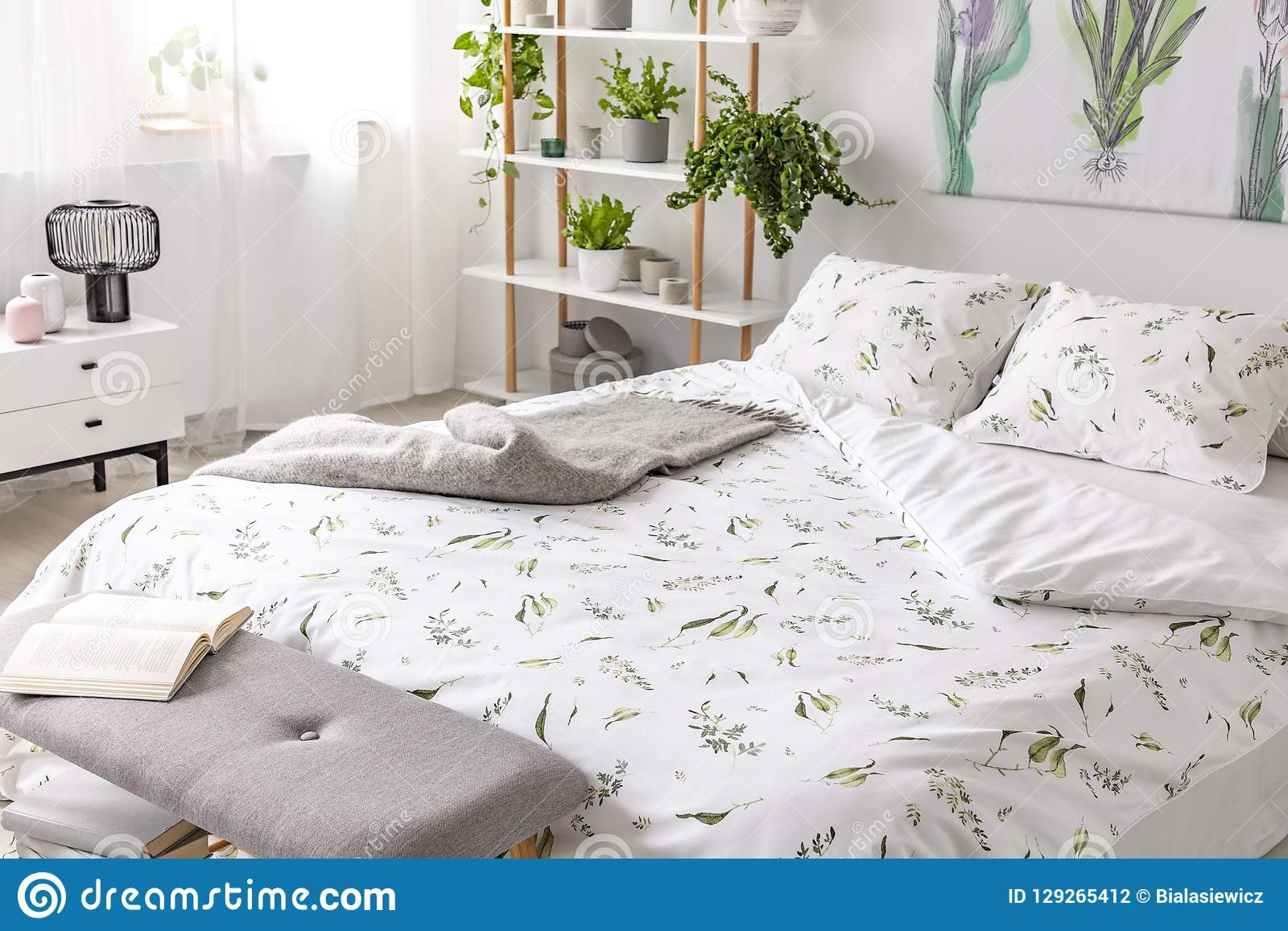Green plant pattern on white bedding and pillows on a bed in a nature loving bedroom interior