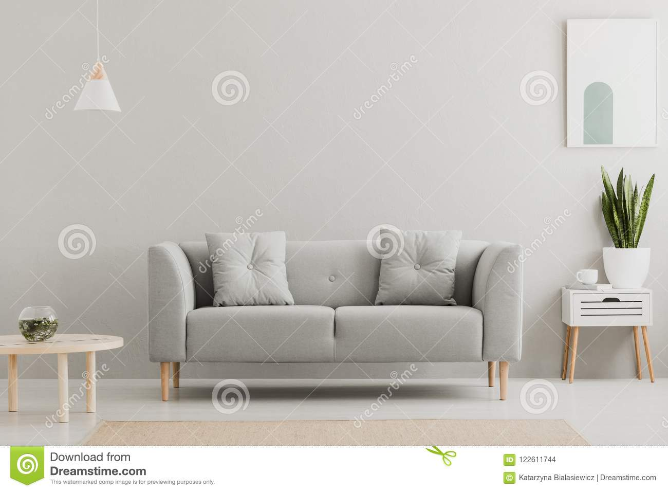Green plant on a scandinavian cabinet with drawer and a cozy couch with pillows in a gray, simple living room interior with place