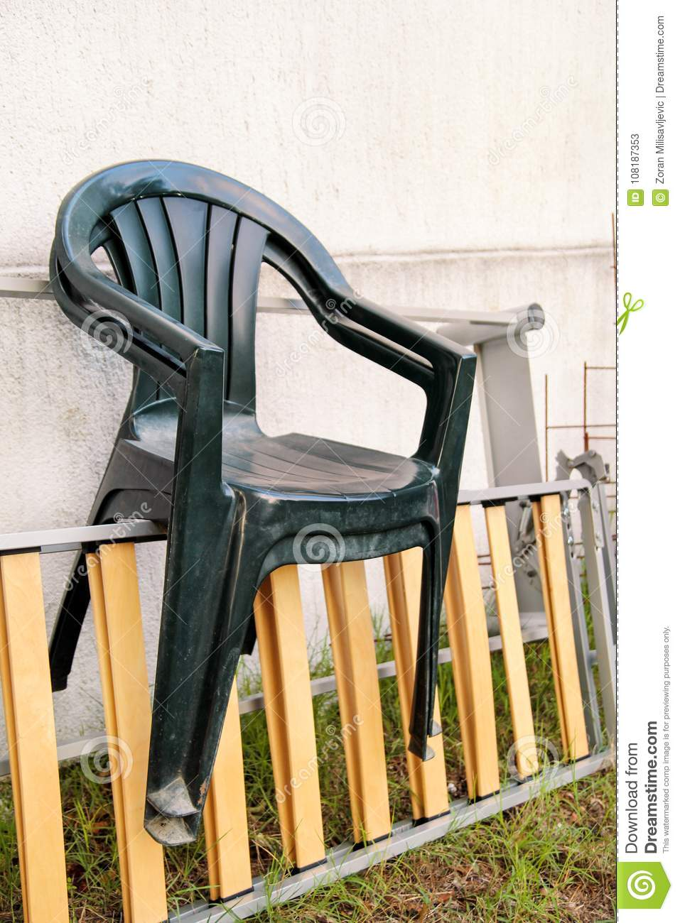 Green Plastic Garden Chairs Thrown Away And Left On A Ladder By
