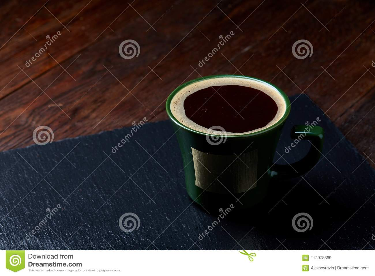 Green porcelain coffee cup on stone board over wooden background, selective focus, close-up