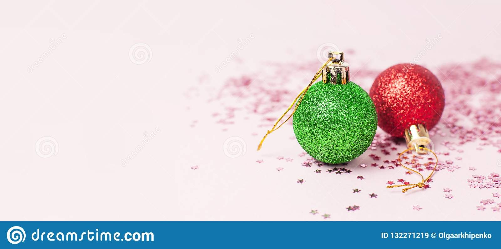Green Red Christmas New Year balls holographic glitter confetti form of stars on pink background Flat Lay copy space. Holiday