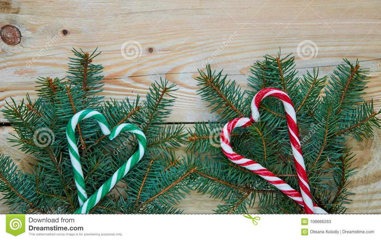 Green and red hearts of candy cones on the Christmas tree branches with copy space. New year or Valentines day sweets decorations