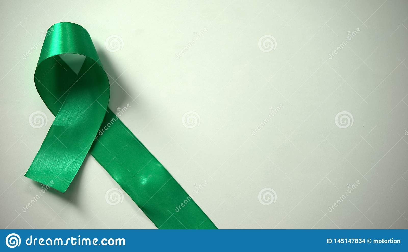 Green ribbon on table, World Mental health day, awareness campaign, tolerance