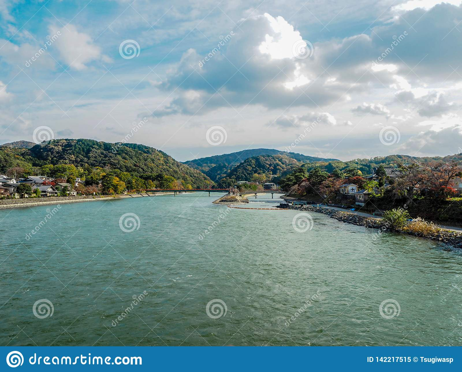 The river in the middle of a small town with mountains and cloudy sky background
