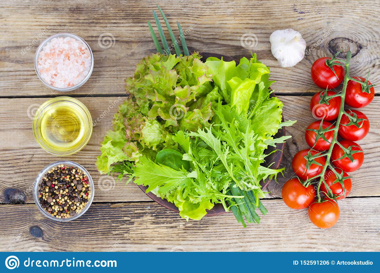 Green salad ingredients organic lettuce, cherry tomatoes, spices and olive oil on wooden background.