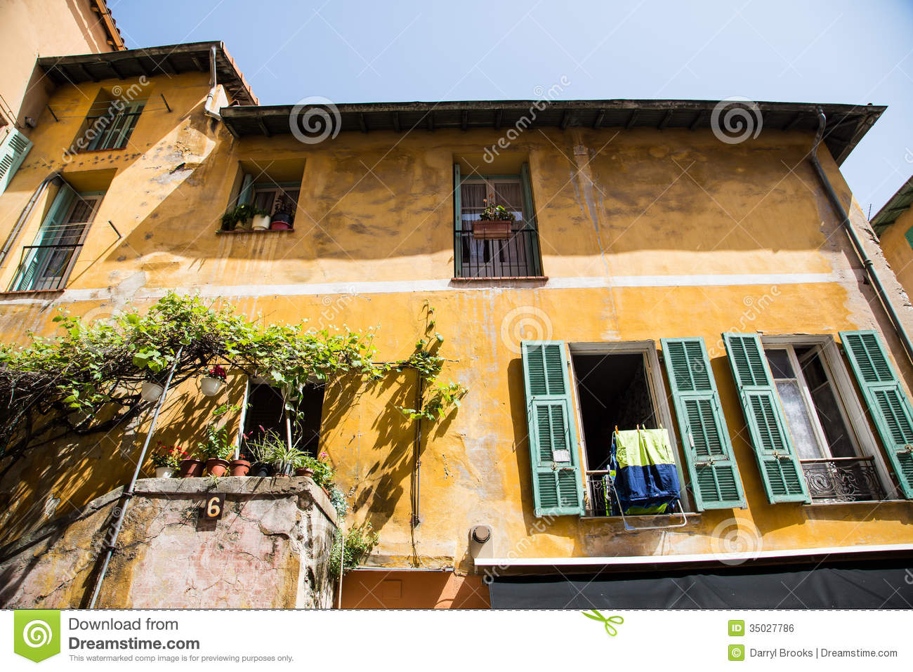 Green Shutters On Open Windows Of Yellow Plaster Building