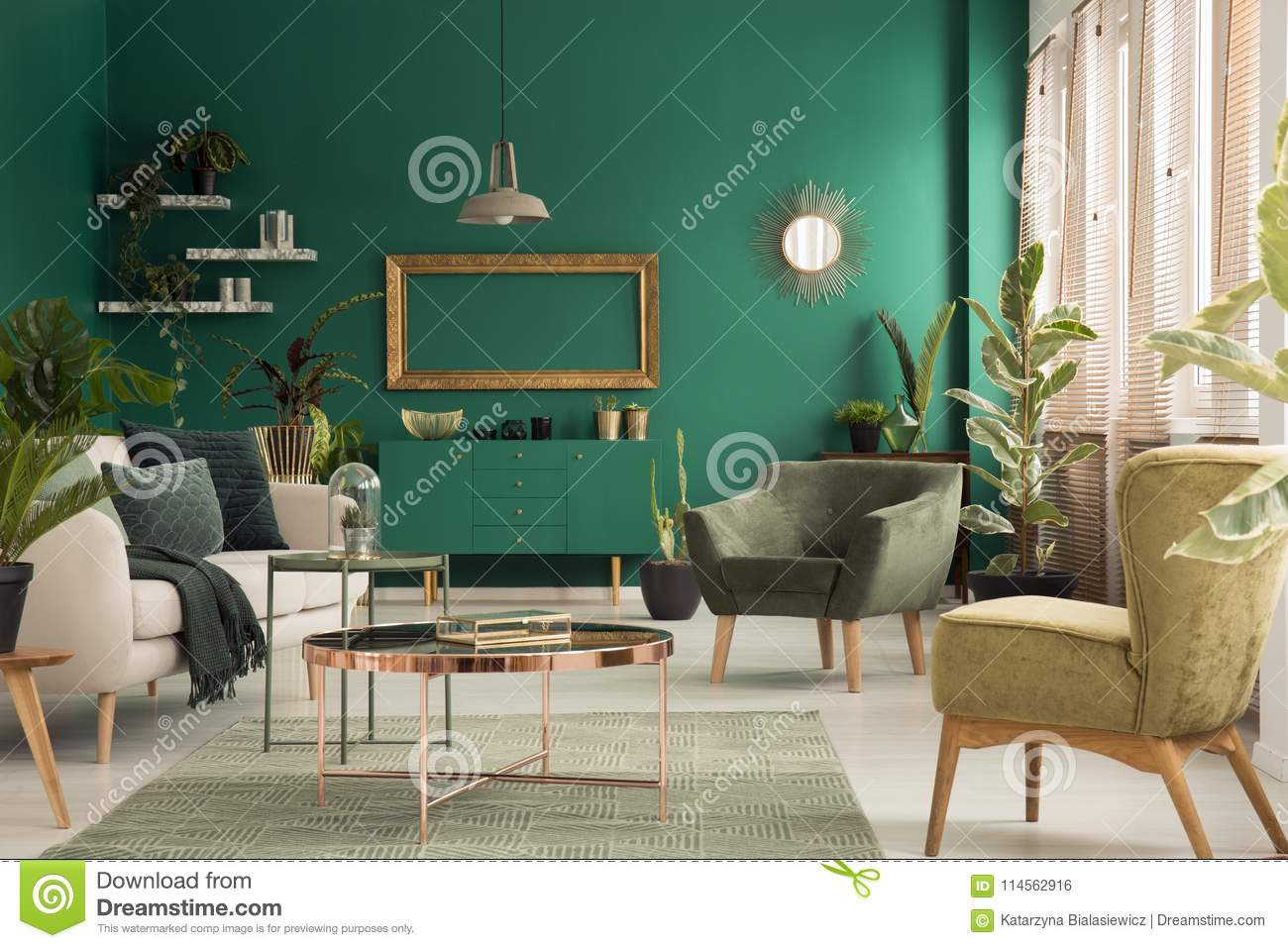 Copper table on rug between beige sofa and armchair in green spacious living room interior with mockup