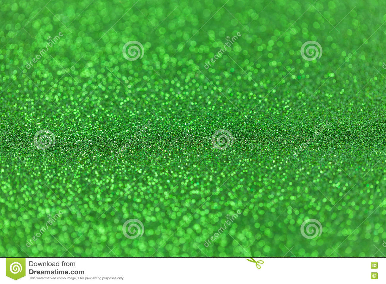 Green sparkling background from small sequins, closeup. Brilliant backdrop