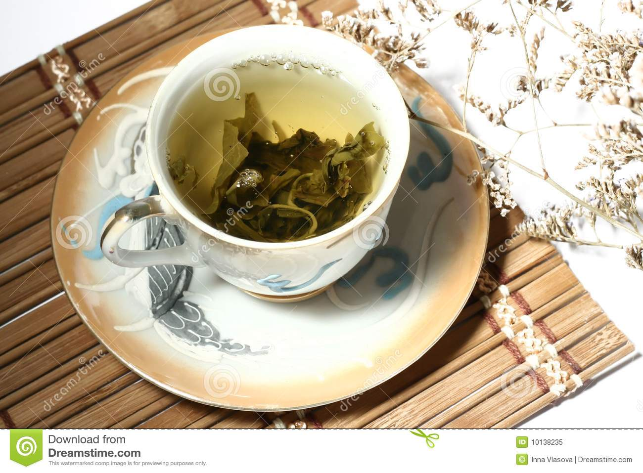 Green tea in a cup with a tea leafs