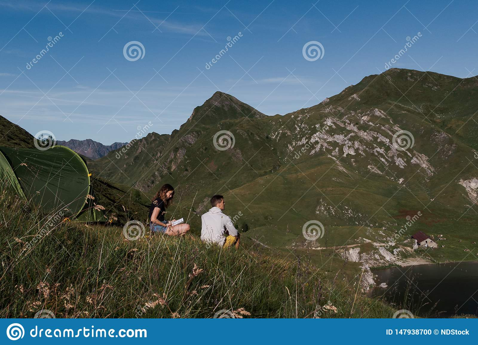 Green tent placed in a peaceful down in the mountains of switzerland. Girl reading a book, boy admires the view