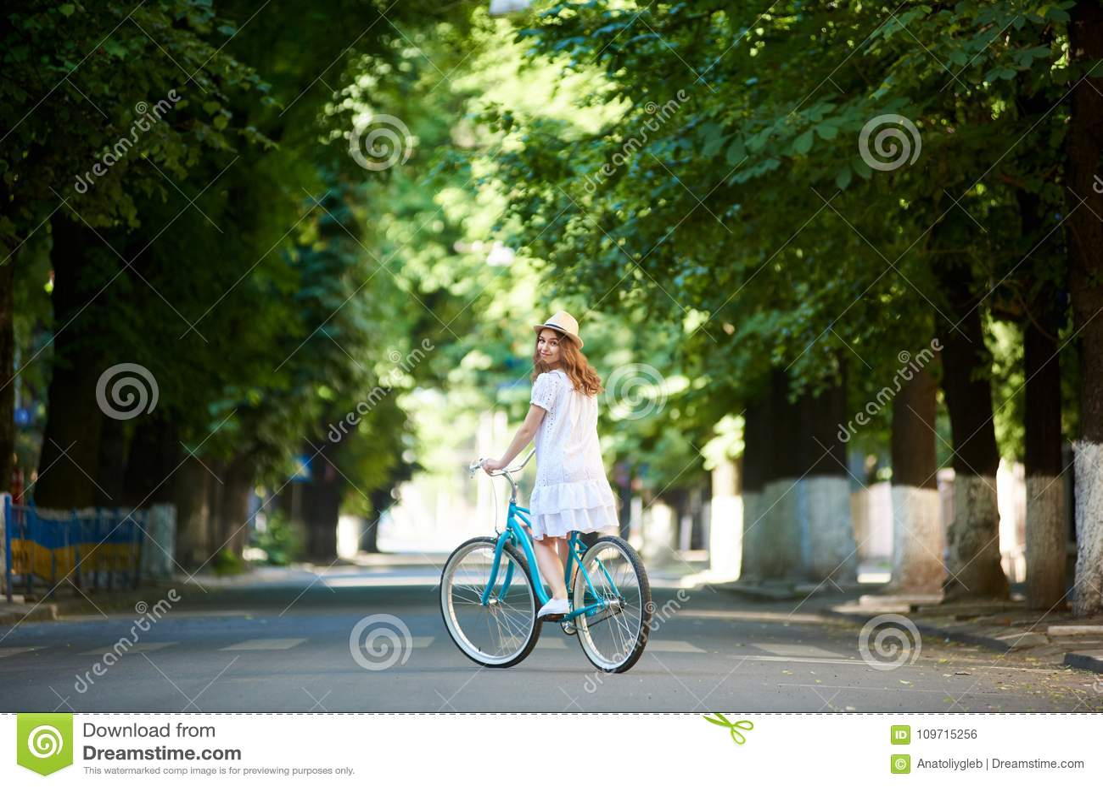 Green urban plantings. Female rides on bike alone at road