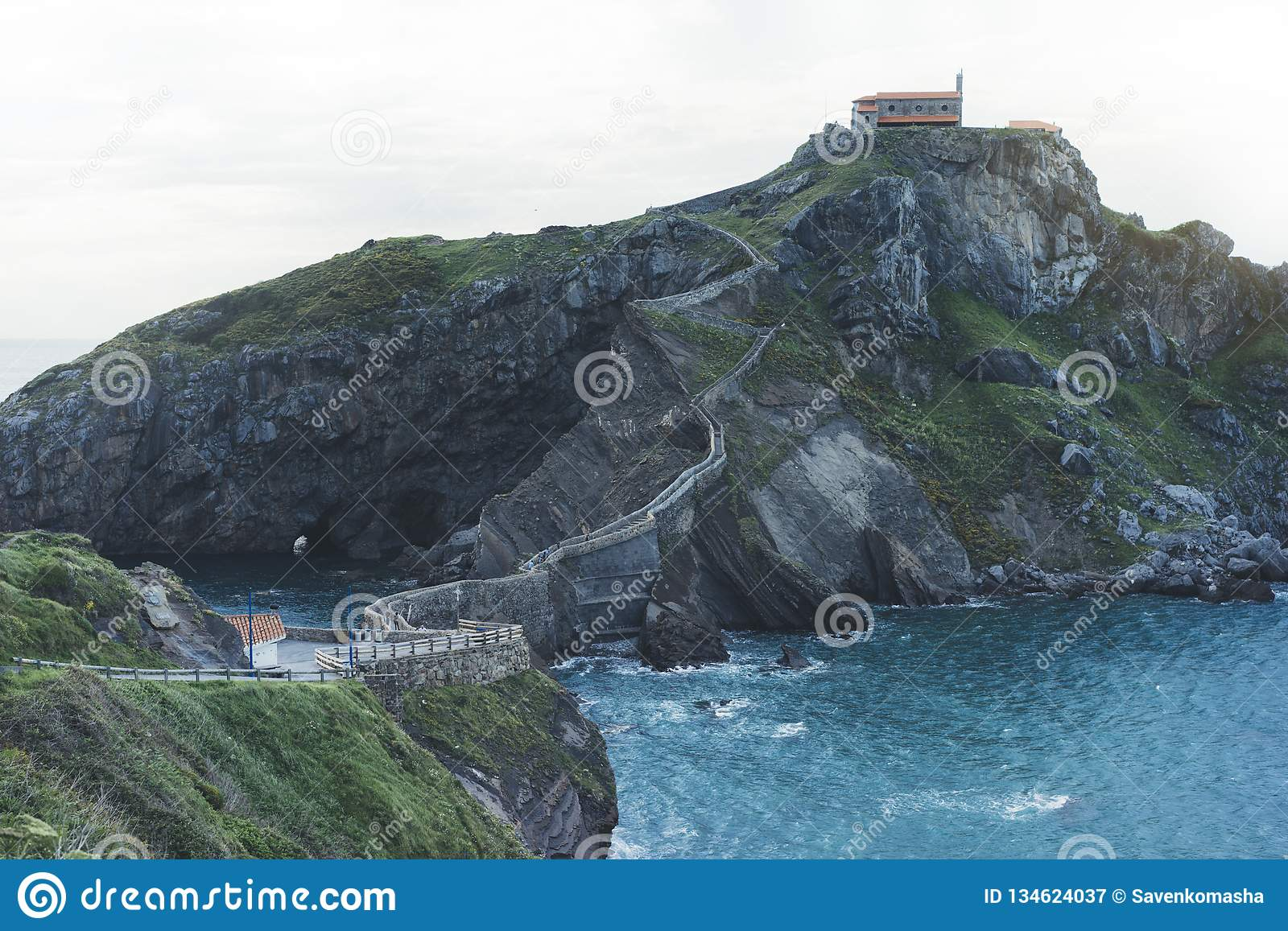 Green valley landscape on background dramatic. View sunlight blue ocean in trip holiday in basque island Gaztelugatxe. Panorama