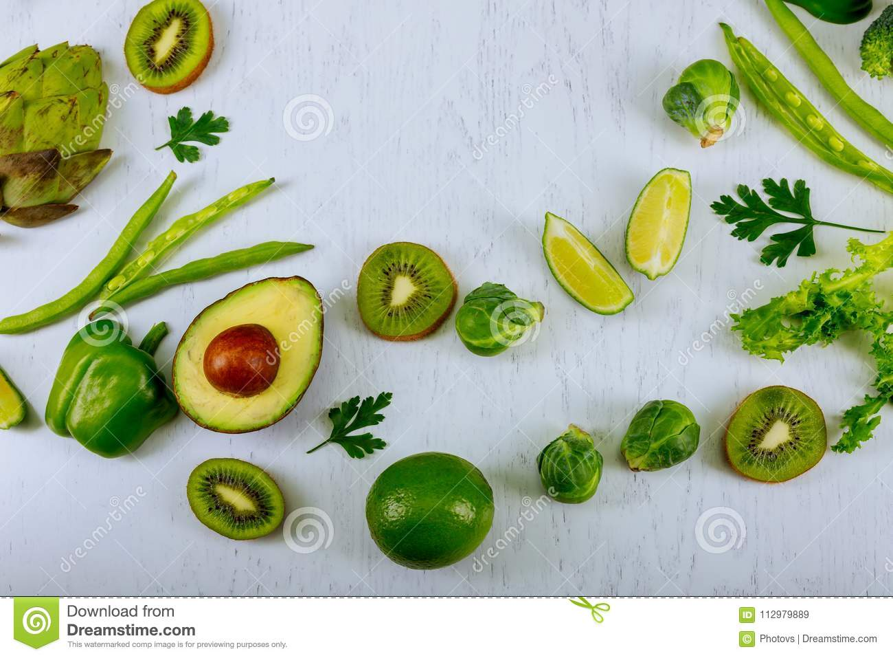 Green vegetables and herbs assortment around wooden cooking board on a white background. Fresh Healthy food. Top view, copy space