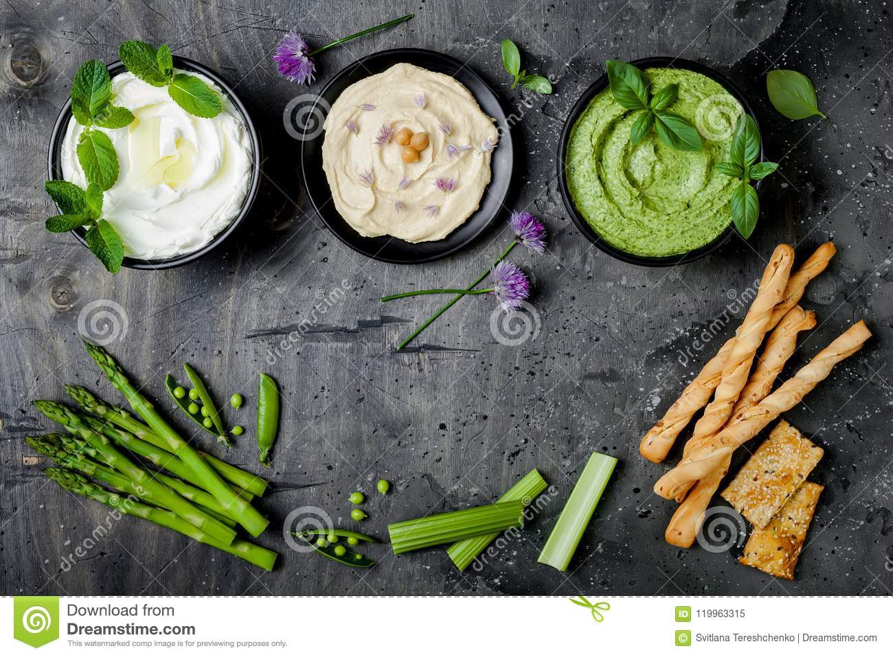Green vegetables raw snack board with various dips. Yogurt sauce or labneh, hummus, herb hummus or pesto with crackers, grissini