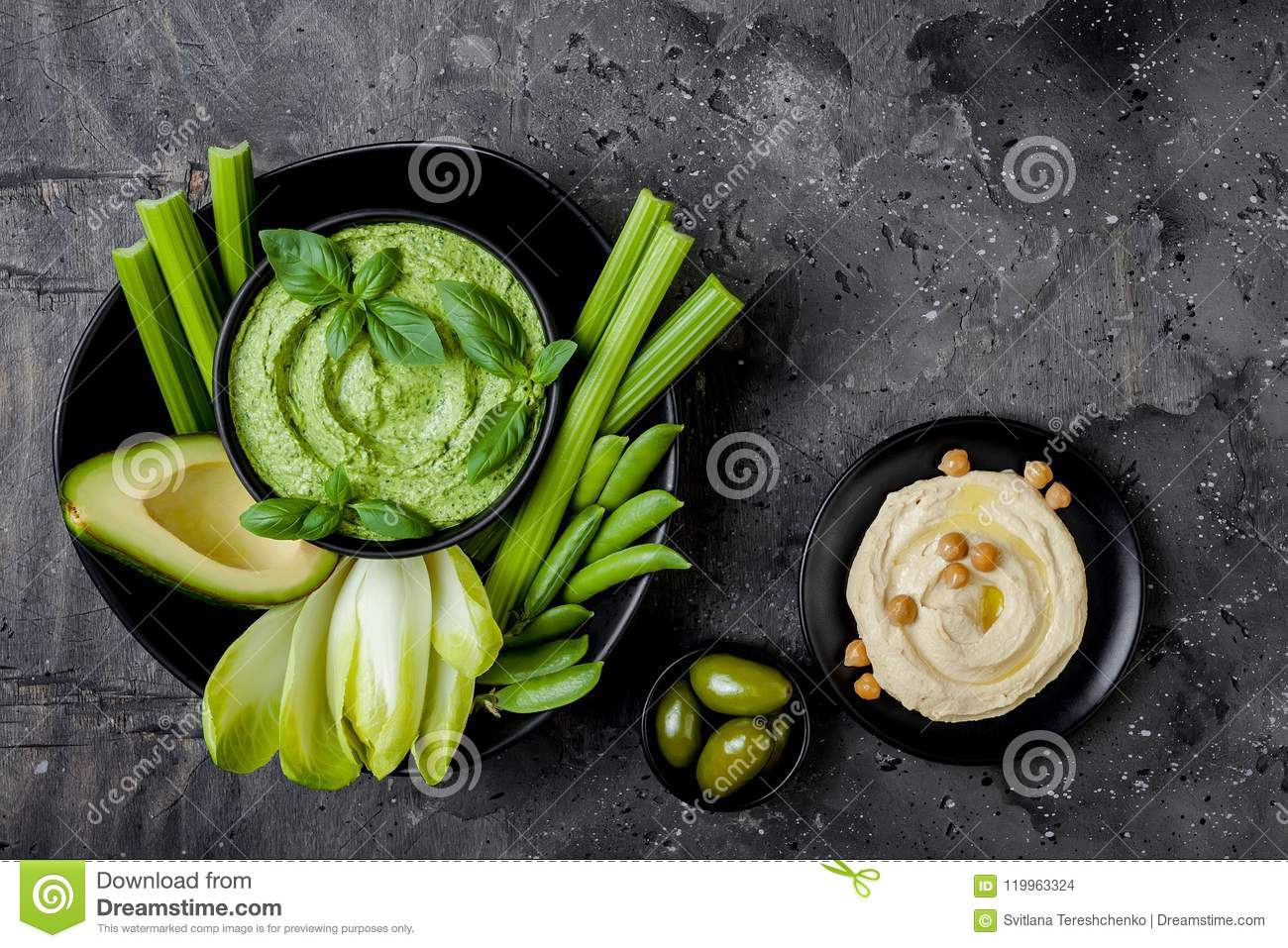 Green vegetables snack board with herb hummus or pesto dip. Healthy raw summer appetizer platter.
